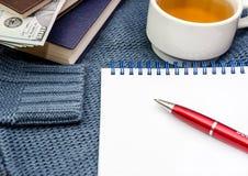 Notatnik, pióro, książki, dolary i filiżanka herbata na błękitnym pulowerze, obraz royalty free