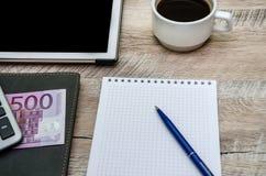 Notatnik, pióro, filiżanka kawy i pieniądze na drewnianym tle, fotografia royalty free