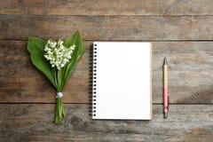 Notatnik, pi?ro i leluja dolina bukiet na drewnianym tle, mieszkanie nieatutowy zdjęcie royalty free