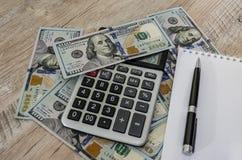 Notatnik, pióro, kalkulator i dolary na drewnianym stole, fotografia stock