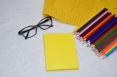 Notatnik, szkła i barwioni ołówki, fotografia stock