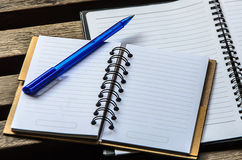 Notatnik z błękitnym piórem na drewnianym stole Fotografia Stock