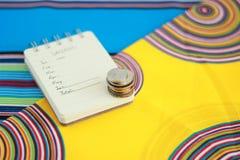 Notatnik z monetami na kolorowym tle zdjęcia stock