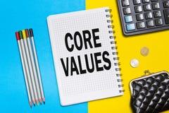 Notatnik z notatki sedna wartościami z biur narzędziami na błękicie żółty tło Pojęcia sedna wartości Obraz Stock