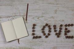 Notatnik z ołówkiem obok inskrypcji kocham ciebie listy ciemne róże Na drewnianym tle, fotografia nad fotografia royalty free