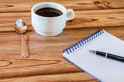 Notatnik z piórem i filiżanka kawy na stole obrazy stock