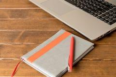 Notatnik z piórem i notatnik na drewnianym stole komputerowy pojęcia e kluczowy laptopu uczenie srebro zdjęcia royalty free