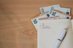 Notatnik z pieniądze i ręki writing na nim zdjęcie stock