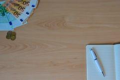 Notatnik z pieniądze i rachunki na stole obrazy royalty free