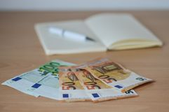 Notatnik z pieniądze i rachunki na stole zdjęcie stock