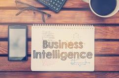Notatnik z tekstem wśrodku business intelligence na stole z co Zdjęcie Royalty Free