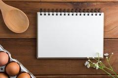 Notatnika biel na drewnianej podłoga z jajkiem Obrazy Royalty Free