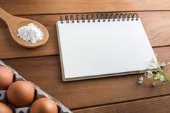 Notatnika biel na drewnianej podłoga z jajkiem Obraz Royalty Free