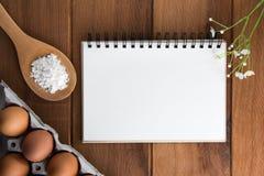 Notatnika biel na drewnianej podłoga z jajkiem Fotografia Stock