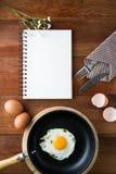Notatnika biel na drewnianej podłoga z jajkiem Zdjęcia Stock