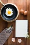 Notatnika biel na drewnianej podłoga z jajkiem Zdjęcia Royalty Free