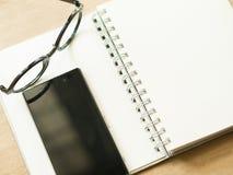 Notatnika eyeglass i czarny mądrze telefon na brązu stole Zdjęcia Royalty Free