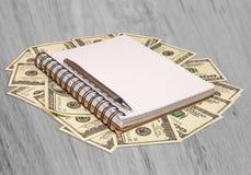 Notatnika pióra Dolara pieniądze na drewnianym stole Obrazy Royalty Free