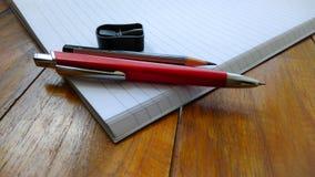 Notatniki, pióra i ołówki na drewnianym, obrazy royalty free