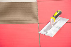 Notched trowel on red tiles Royalty Free Stock Image