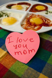 Note. Breakfast for mother. Fried eggs and note I love you mom on the table Royalty Free Stock Images