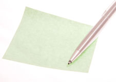 Note. Green, empty note paper with a metal pen isolated on white stock image