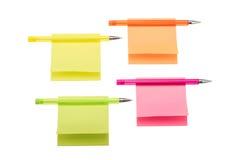 Note appiccicose colorate con le penne del biro fotografia stock