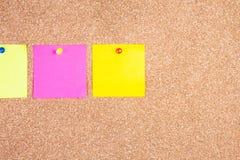 Note appiccicose di ricordo multicolore sul bordo del sughero Immagine Stock