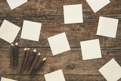 Note appiccicose e matite colorate su fondo d'annata Fotografie Stock