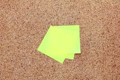 Note appiccicose gialle su un bordo del sughero Fotografie Stock