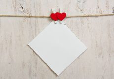 Note attached with two red hearts clothespins Royalty Free Stock Image