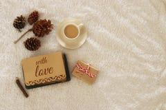Note avec le texte : AVEC L'AMOUR et la tasse de cappuccino au-dessus de tapis confortable et chaud de fourrure Vue supérieure Images libres de droits