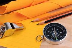 Note blanche de corde, d'écharpe, de sifflement, de boussole, de crayon et de papier de scout d'ordre photos stock