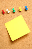 Note and Board. A message board background with a yellow post-it sticky note on it and push-pins stock photography