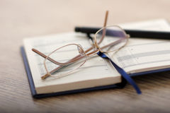 Note-book. Glasses and a pen on a wooden table Stock Photography