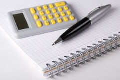 Note book with checked pages, pen and calculator Stock Images