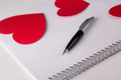 Note book with checked pages, pen and paper hearts Royalty Free Stock Images
