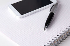 Note book with checked pages, pen and smart phone Royalty Free Stock Images