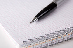 Note book with checked pages and pen Stock Photos