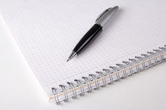 Note book with checked pages and pen on the table Stock Image