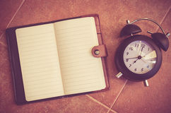 Note book and clock on the floor Stock Images