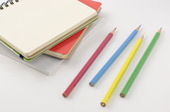 Note book and colored pencils. Stock Images