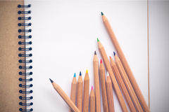 Note book and colored pencils Royalty Free Stock Images
