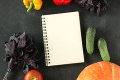 Note book and composition of vegetables on black board. Royalty Free Stock Photos