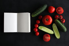 Note book and composition of vegetables on black wooden desk. Stock Image