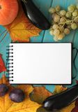 Note book and composition of vegetables on blue wooden desk. Royalty Free Stock Image