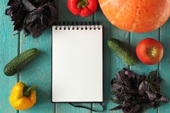 Note book and composition of vegetables on blue wooden desk. Stock Images