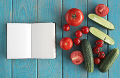 Note book and composition of vegetables on blue wooden desk. Royalty Free Stock Photography
