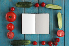 Note book and composition of vegetables on blue wooden desk. Royalty Free Stock Photos