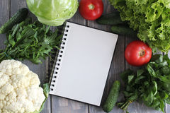 Note book and composition of vegetables on grey wooden desk. Stock Photography